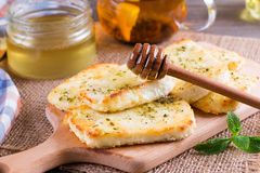 Grilled haloumi cheese with herbs on a cutting board. Grilled haloumi cheese with herbs and honey on a cutting board Royalty Free Stock Photography