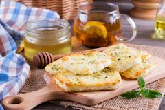 Grilled haloumi cheese with herbs on a cutting board. Grilled haloumi cheese with herbs and honey on a cutting board Stock Image