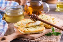 Grilled haloumi cheese with herbs on a cutting board. Grilled haloumi cheese with herbs and honey on a cutting board Royalty Free Stock Photos