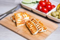 Grilled haloumi cheese on a wooden board with olives, cherry, cucumbers and pepperoni. Close-up. Selective focus Stock Photos
