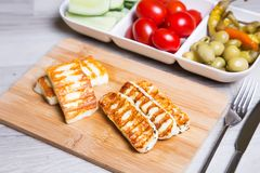 Grilled haloumi cheese on a wooden board with olives, cherry, cucumbers and pepperoni. Close-up. Selective focus Stock Photo