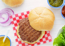 Grilled hamburger with condiments h. Royalty Free Stock Images