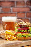 Grilled hamburger with fries and beer on brick wall background Royalty Free Stock Photography