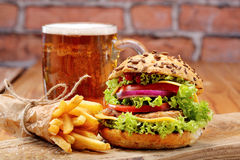 Grilled hamburger with fries and beer Royalty Free Stock Images
