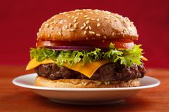 Grilled hamburger. Homemade grilled hamburger on plate with red background Royalty Free Stock Photos