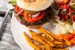 Grilled Hamburger with Sweet Potato Friesh organic salad. Top view of freshly grilled hamburger with cheddar cheese, organic tomatoes and lettuce, red onion stock photo