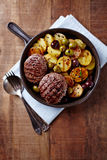 Grilled Hamburgers with Potatoes served in a Ceramic Dish Stock Photo