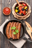Grilled homemade sausages in a frying pan and salad fresh vegetables Royalty Free Stock Photos