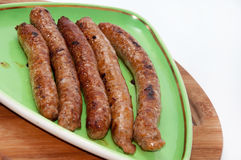 Grilled homemade sausages served on green plate Royalty Free Stock Image