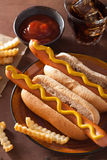 Grilled hot dogs with mustard and french fries Royalty Free Stock Image