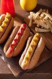Grilled hot dogs with mustard ketchup and french fries Royalty Free Stock Image