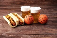 Grilled hot dogs with mustard and ketchup on the table with draft beer. Television watching basketball game with eating snacks and