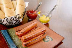 Grilled hot dogs ready to serve. Grilled hot dogs stacked on a plate ready to serve with condiments ketchup and mustard and buns Royalty Free Stock Photos
