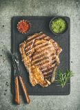Grilled hot rib-eye beef steak on bone with chimichurri sauce. Flat-lay of grilled hot rib-eye beef steak on bone with chimichurri green sauce and hot red chili Royalty Free Stock Photo