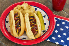 Grilled hotdogs at a patriotic cookout. A must-have at American holiday cookouts, these hotdogs are dressed with ketchup and mustard and are served with potato royalty free stock photography
