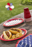 Grilled hotdogs at a patriotic holiday BBQ. American holiday cookout with hotdogs that are topped with ketchup and mustard and are served with potato chips. One royalty free stock photo