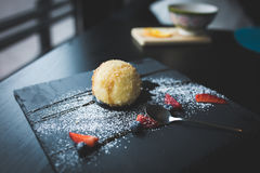 Grilled ice-cream in coconut with sauce on black stone plate. Asian food background. Eating concept. Restaurant place Royalty Free Stock Image
