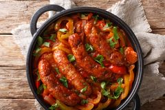 Grilled Italian sausages with bell pepper close-up in a pan. horizontal top view stock photography