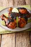 Grilled jerk chicken drumstick with lime and onions closeup on a Stock Image