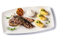 Grilled juicy mackerel, served with mashed potatoes, lemon, and tartar sauce. Microgreen. Modern pitch on a white tarekle. On a white background. beautiful stock image