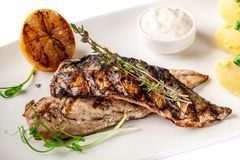 Free Grilled Juicy Mackerel, Served With Mashed Potatoes, Lemon, And Tartar Sauce. Microgreen. Modern Pitch On A White Tarekle Royalty Free Stock Images - 139049909