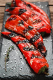 Grilled juicy red paprika. Vegetarian food menu. Appetizing and juicy grilled pepper served on black slate, close up view. Restaurant menu photo. Vegetarian Royalty Free Stock Image