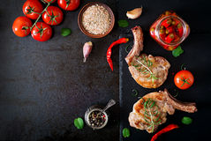 Grilled juicy steak on the bone with vegetables on a dark background. Royalty Free Stock Photography