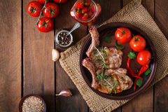 Grilled juicy steak on the bone with vegetables on a wooden background. Stock Image