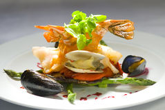 Grilled Jumbo Shrimp. A dish of grilled jumbo lump shrimp served with baby watercress, roasted red bell pepper, oysters, mussels, asparagus and beetroot sauce Stock Photography