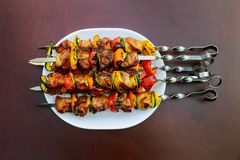 Grilled kebab cooking on metal skewer closeup. Roasted meat cooked at barbecue. BBQ fresh beef meat chop slices. Traditional eastern dish, shish kebab Royalty Free Stock Photos