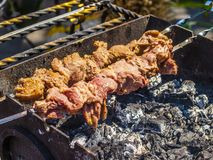 Shish kebab on skewers. Grilled kebab cooking on metal skewer closeup. Roasted meat cooked at barbecue. Grill on charcoal and flame, picnic, street food Royalty Free Stock Photo
