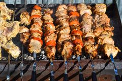 Grilled kebab cooking on metal skewer closeup. Roasted meat cooked at barbecue. Traditional eastern dish, shish kebab. Grill on ch. Arcoal and flame, picnic Stock Photo