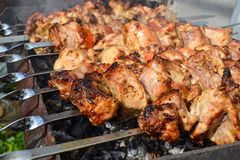 Grilled kebab cooking on metal skewer closeup. Roasted meat cooked at barbecue. Traditional eastern dish, shish kebab. Grill on ch. Arcoal and flame, picnic Stock Image