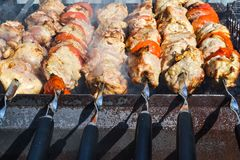 Grilled kebab cooking on metal skewer closeup. Roasted meat cooked at barbecue. Traditional eastern dish, shish kebab. Grill on ch. Arcoal and flame, picnic Royalty Free Stock Photography