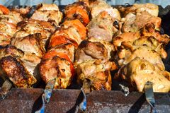 Grilled kebab cooking on metal skewer closeup. Roasted meat cooked at barbecue. Traditional eastern dish, shish kebab. Grill on ch. Arcoal and flame, picnic Royalty Free Stock Image