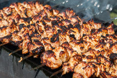 Grilled kebab cooking on metal skewer. Roasted meat cooked at barbecue. BBQ fresh beef meat chop slices. Grill on charcoal and flame, picnic, street food Stock Images