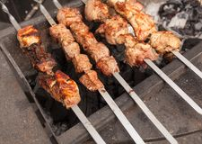 Grilled kebab cooking on metal skewer. Roasted meat cooked at barbecue. BBQ fresh beef meat chop slices. Traditional eastern dish, Stock Images