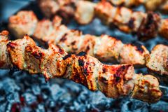 Grilled kebab cooking on metal skewer. Roasted meat cooked at barbecue. Traditional eastern dish, shish kebab. Grill on. Grilled kebab cooking on metal skewer Royalty Free Stock Photography