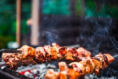 Grilled kebab cooking on metal skewer. Roasted meat cooked at barbecue. Traditional eastern dish, shish kebab. Grill on. Grilled kebab cooking on metal skewer Stock Images