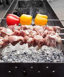 Grilled kebab cooking on metal skewer. Roasted meat cooked at barbecue. with Red and yellow Bell pepper. Grilled kebab cooking on metal skewer. Roasted meat Royalty Free Stock Photography