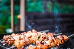 Grilled kebab cooking on metal skewer. Roasted meat cooked at barbecue. Traditional eastern dish, shish kebab. Grill on. Grilled kebab cooking on metal skewer Royalty Free Stock Images