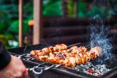Grilled kebab cooking on metal skewer. Roasted meat cooked at barbecue. Traditional eastern dish, shish kebab. Grill on. Grilled kebab cooking on metal skewer Royalty Free Stock Photos