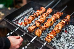 Grilled kebab cooking on metal skewer. Roasted meat cooked at barbecue. Traditional eastern dish, shish kebab. Grill on. Grilled kebab cooking on metal skewer Royalty Free Stock Image