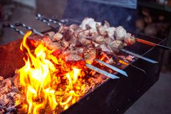 Grilled kebab cooking on metal skewers grill. Royalty Free Stock Images