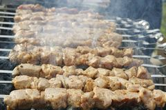 Grilled kebab cooking on metal skewers grill. stock images
