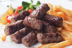 Grilled kebab with french fries. Grilled kebab, turkish style barbecued meat with fried potato Royalty Free Stock Image