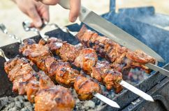 Grilled kebab frying on metal skewers. Roasted meat cooked at barbecue with smoke. Close up stock images