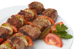 Grilled kebab with vegetables. Kebab served with grilled vegetables on white plate, selective focus Stock Photo