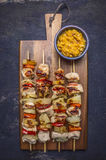 Grilled kebabs with peppers, pork and pineapple on a cutting board with sauce on wooden rustic background top view close up Stock Photos