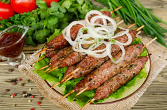 Grilled kebabs on wooden skewers and fresh vegetables Royalty Free Stock Image